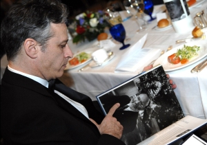 Jon Stewart at a table that is clearly not a Seder Table as there are rolls present.